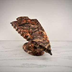 Three piece skull plaque with an arrowhead shaped panel and a camouflage design.